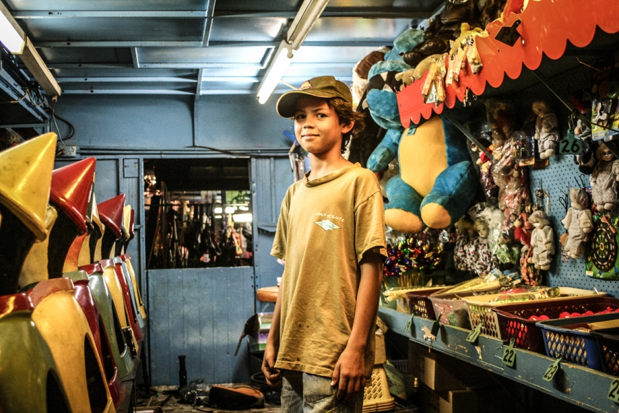 a boy on the night market at mindil beach in darwin australia stands among toys